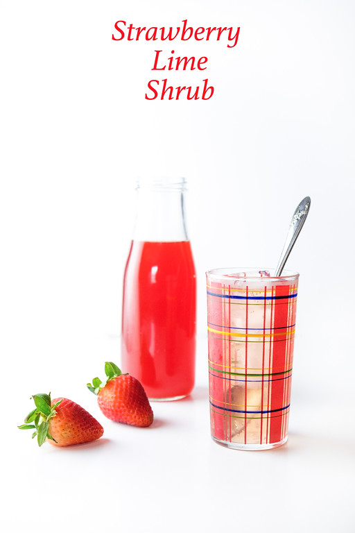 A bottle of deep red strawberry lime shrub, with a glass and two strawberries.