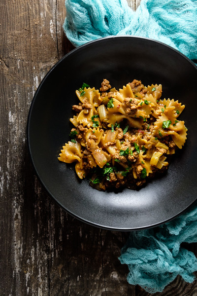 black bowl filled with pasta and pork on a wooden background.