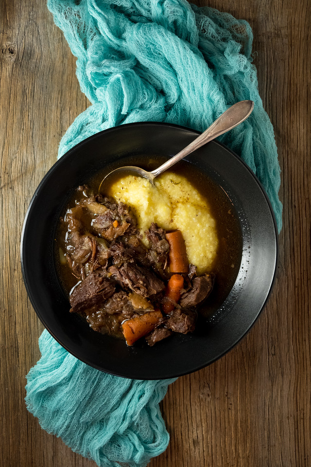 Bowl filled with red wine beef stew over polenta