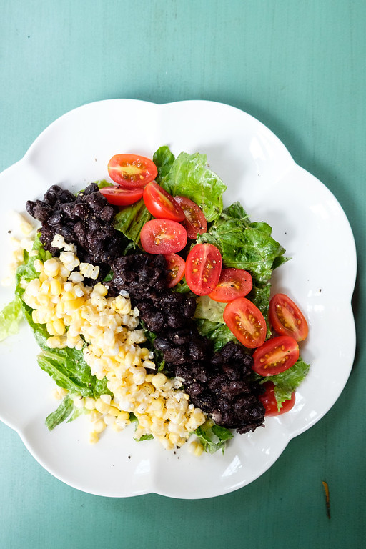 White plate with corn, black beans and tomatoes arranged in rows on top of lettuce.