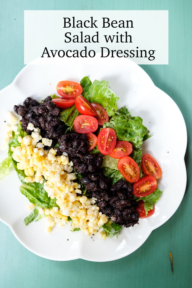 Corn, black beans and tomatoes arranged over lettuce with text overlay reading Black Bean Salad with Avocado Dressing