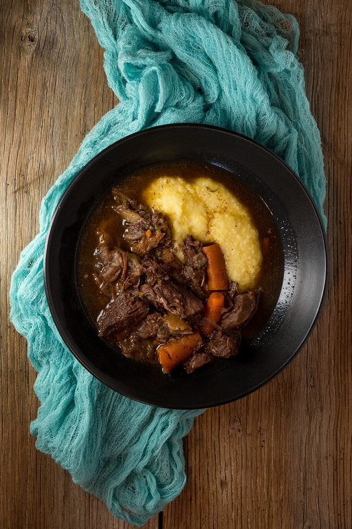 Bowl of beef stew and polenta on wooden background with blue scarf.