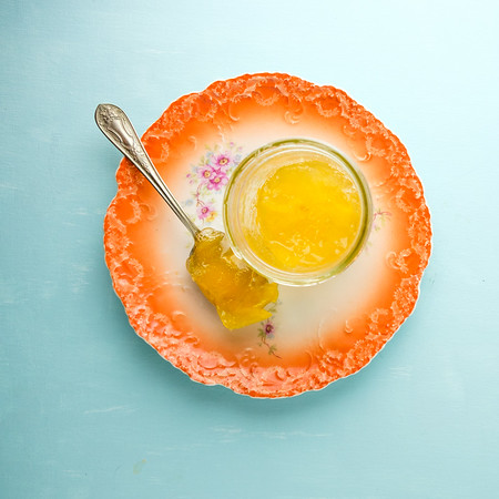 Jar of orange colored marmalade with a spoon on an orange plate on a blue background.