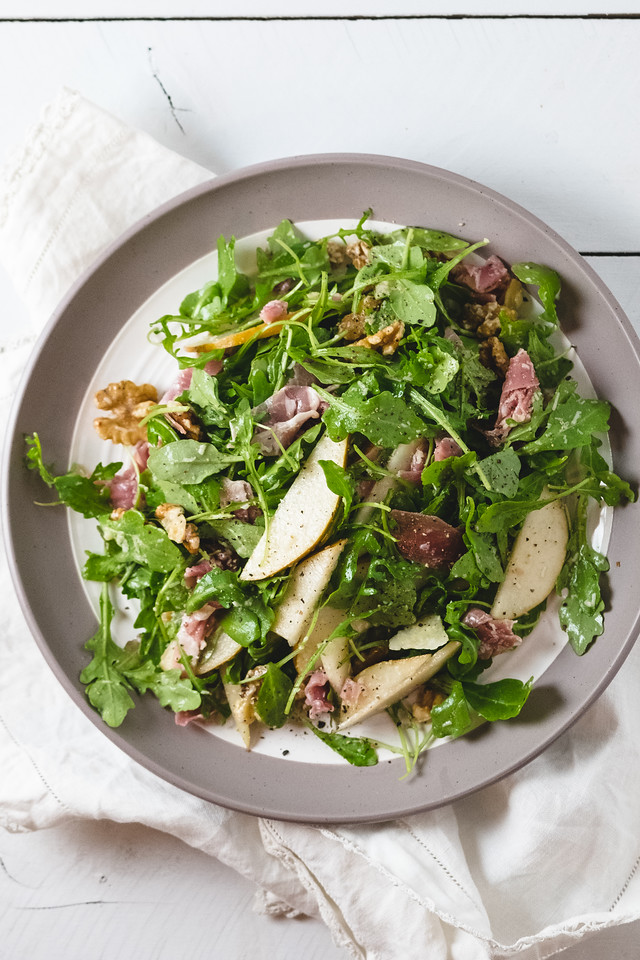Plate of salad with arugula, pears, prosciutto