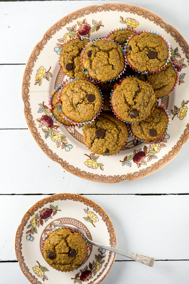 Overhead shot of two plates with pumpkin muffins with chocolate chips.