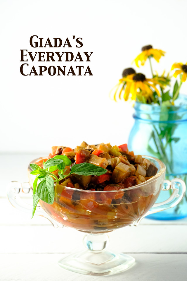 Bowl of Caponata with yellow flowers in a blue jar with text overlay reading Giada's Everyday Caponata