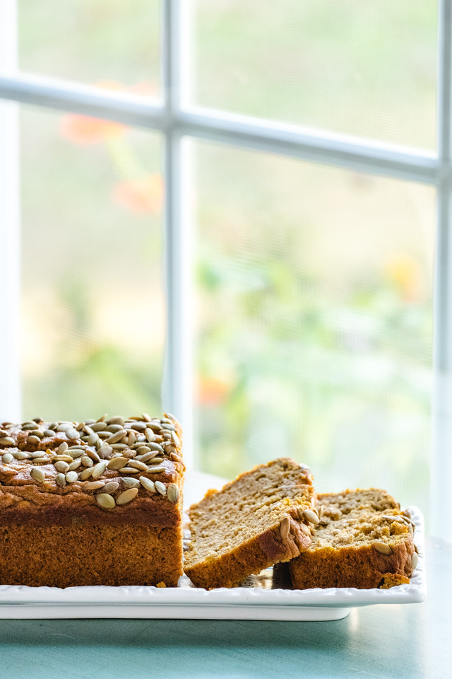 Sliced pumpkin bread in front of a window