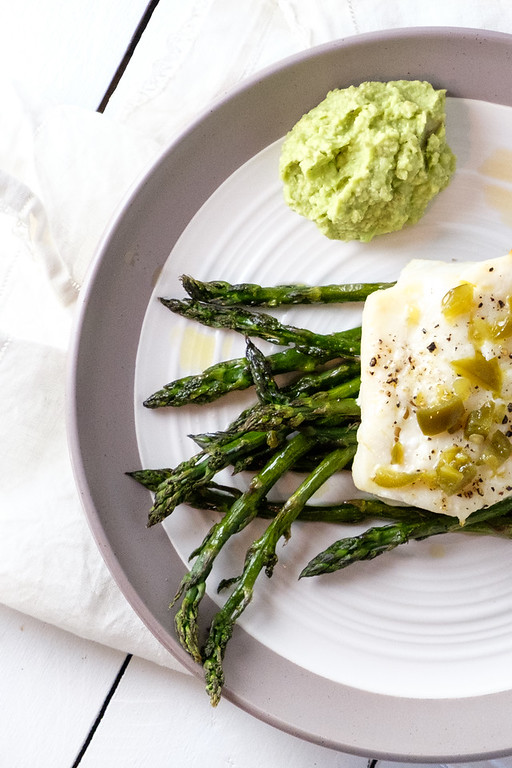 Plate with asparagus topped with cod and a bright green mound of avocado puree.