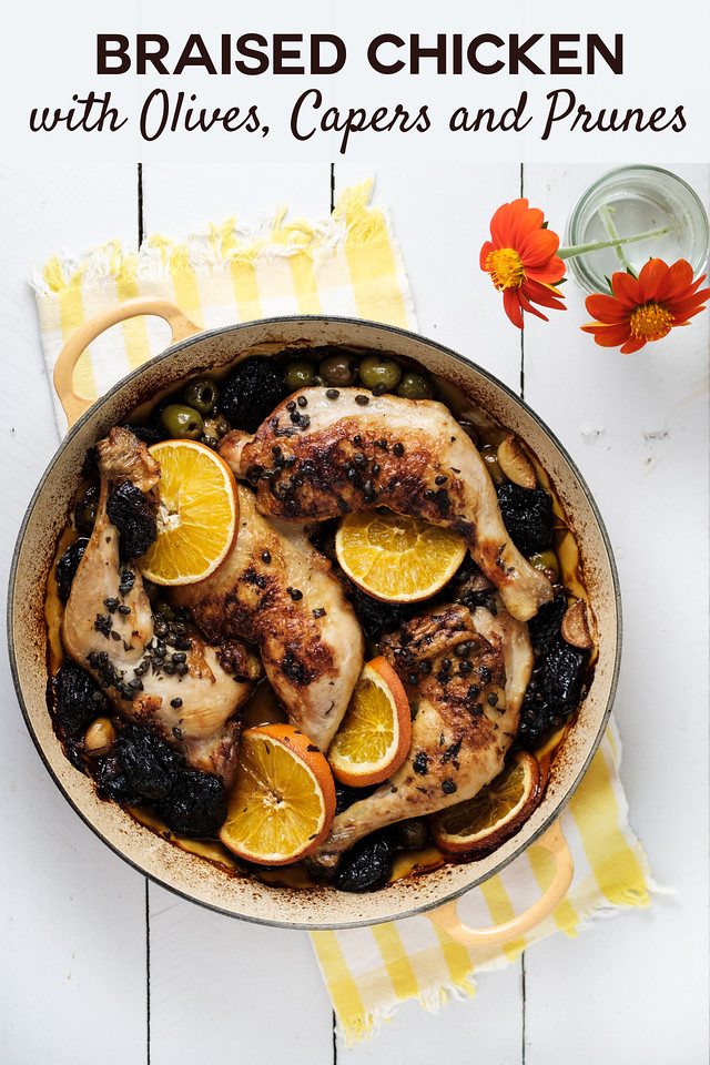 Braising pan with chicken leg quarters, prunes, olives and orange slices on white background, with flowers in a vase and text overlay.
