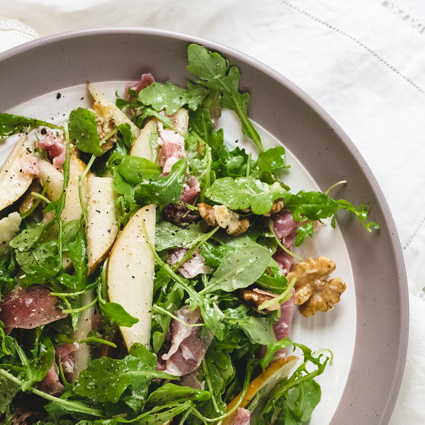 Plate of arugula salad with pears, walnuts and prosciutto