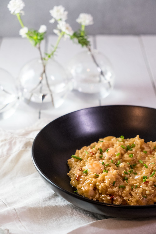 Dark bowl filled with shrimp risotto and a flower vase