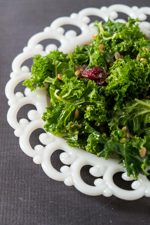 White scalloped plate with dark green kale salad and a dried cranberry on top.