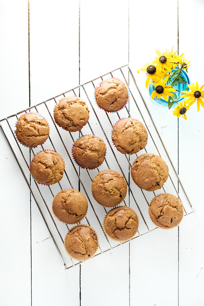 Cranberry Pumpkin Muffins on a cooling rack with a vase of flowers