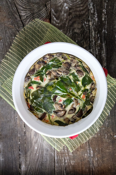 Frittata in a white bowl on a wooden background.