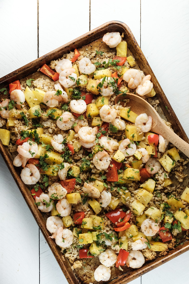 Sheet pan with shrimp, bell peppers, pineapple and rice.