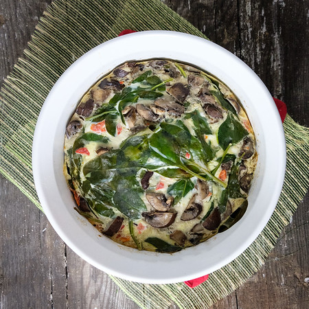 White casserole dish with spinach and mushrooms in a frittata on old wood.