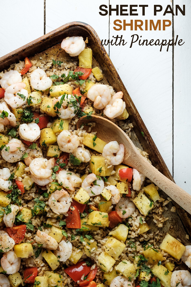 Sheet pan with shrimp, bell peppers and pineapple with brown rice. Text overlay reading Sheet Pan Shrimp with Pineapple