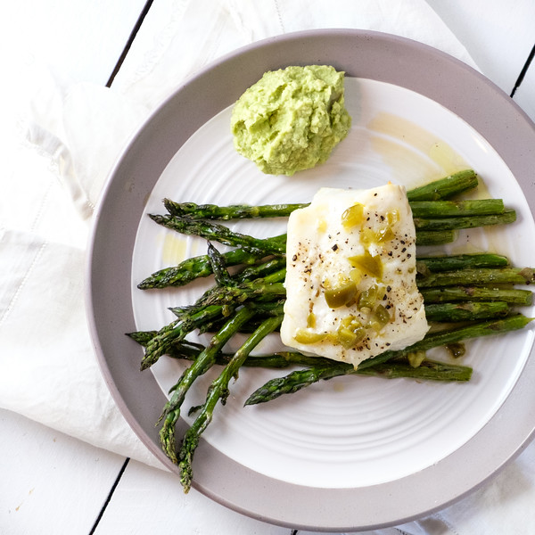 Plate with cod, asparagus and bright green dressing.