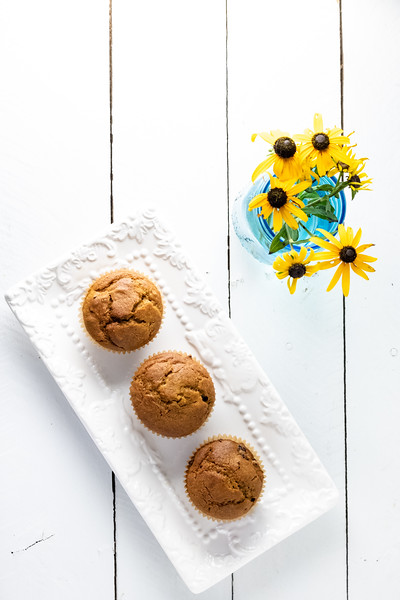 Three muffins on a white tray with a vase of flowers