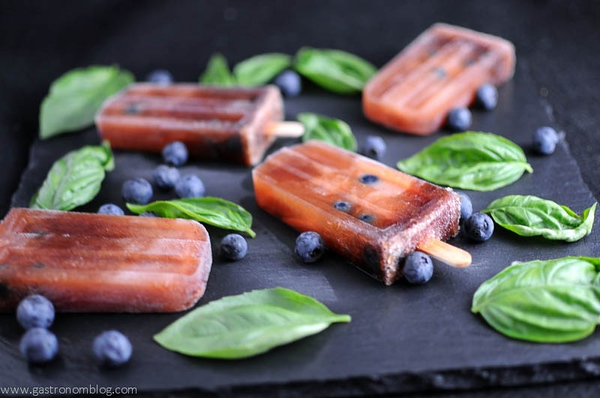 Deep red popsicles with blueberries and basil leaves