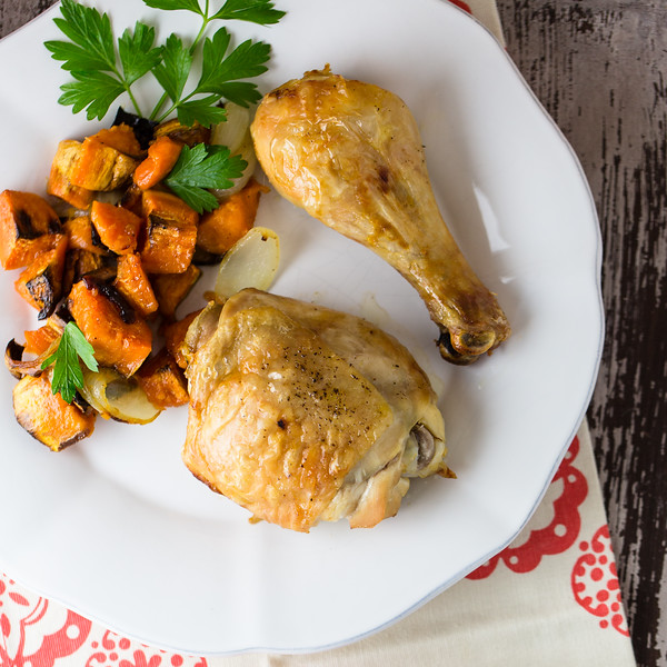 White plate with chicken and sweet potatoes.