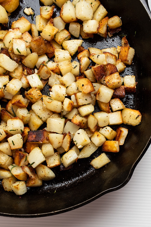 Cast iron skillet with fried potatoes.
