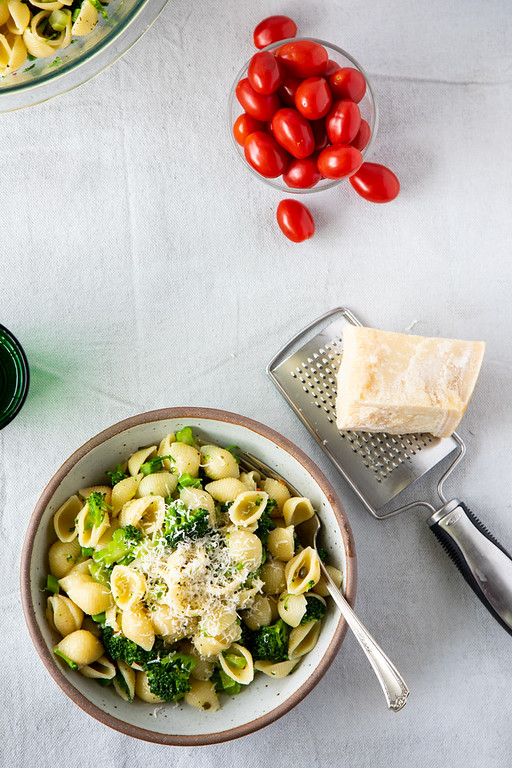 Bowl of pasta with broccoli and capers with a chunk of parmesan cheese.