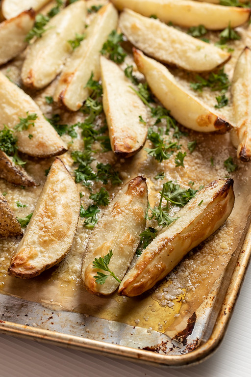 Sheet pan with golden brown potato wedges topped with Parmesan cheese and parsley.