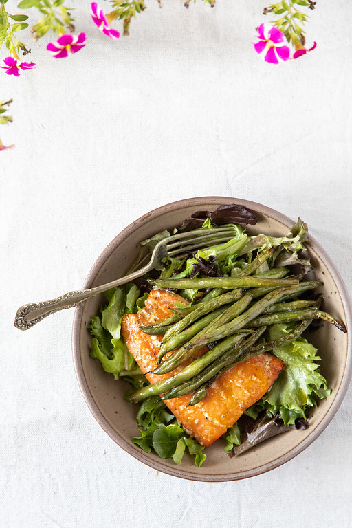Bowl of salmon and green beans on lettuce.