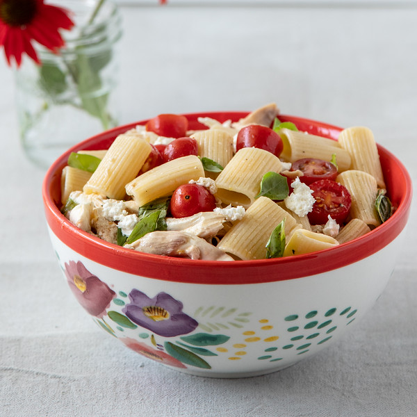 Red bowl filled with a caprese chicken pasta salad.