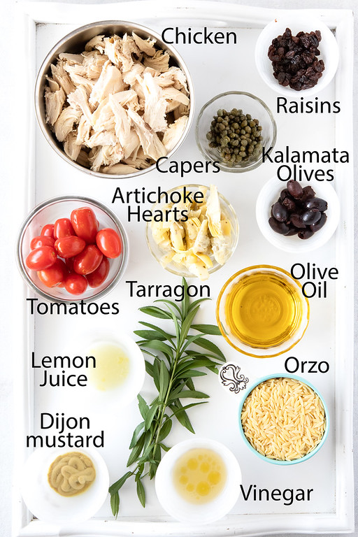 All of the ingredients needed to make Mediterranean Chicken Salad on a white surface and labeled.