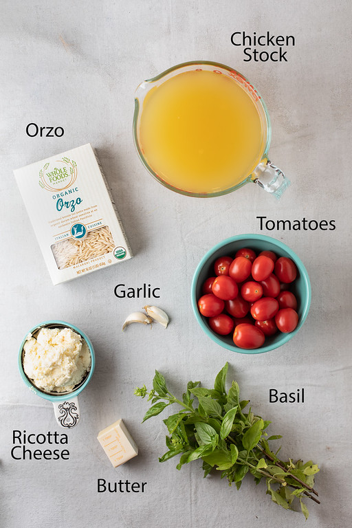 Orzo, chicken stock, tomatoes, garlic, ricotta cheese, butter and basil - ingredients to make orzo pasta recipe.