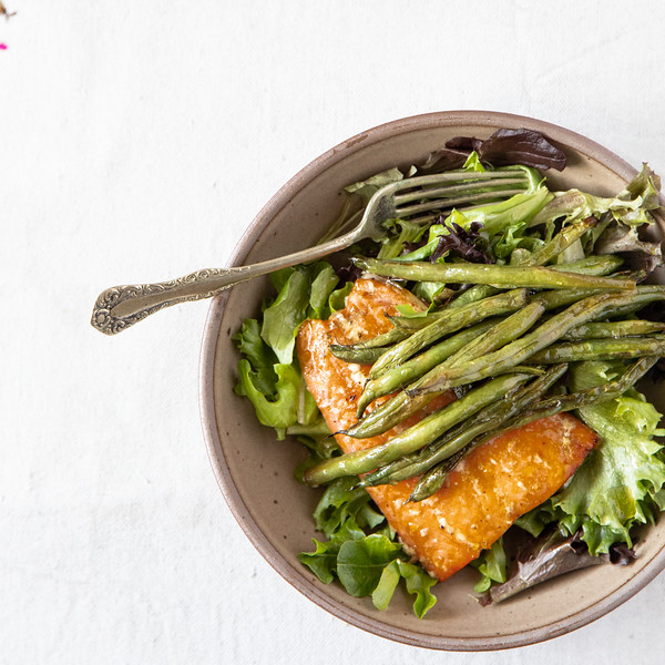 Bowl of lettuce topped with salmon and green beans.