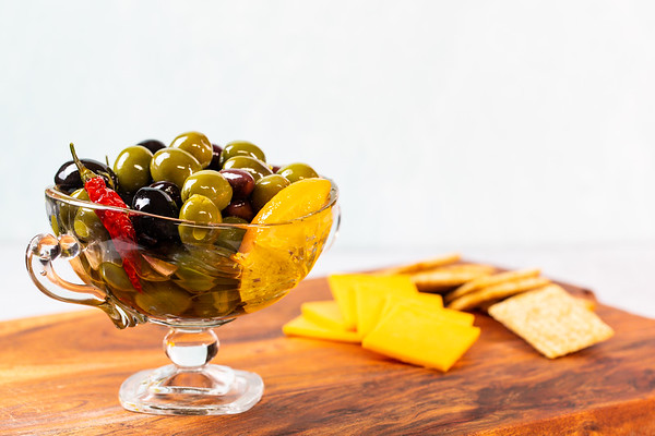 Bowl of marinated olives on a board with cheese and crackers.
