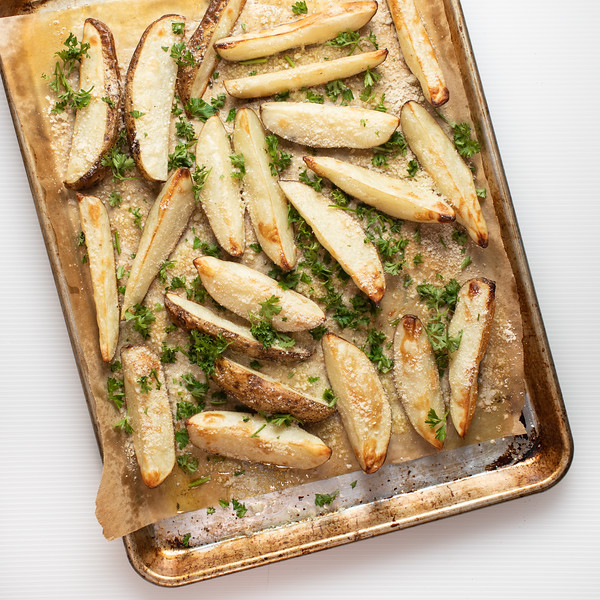 Sheet pan with oven baked fries sprinkled with parsley and Parmesan cheese.