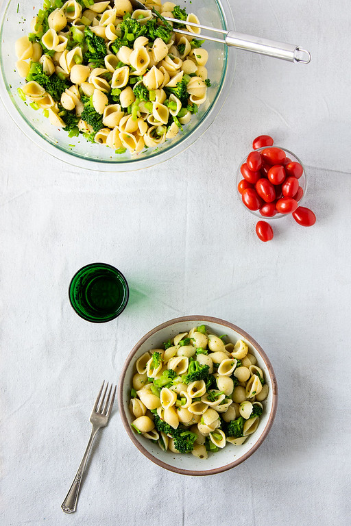 Two bowls of pasta with broccoli with capers, a small green drinking glass and a bowl of cherry tomatoes.