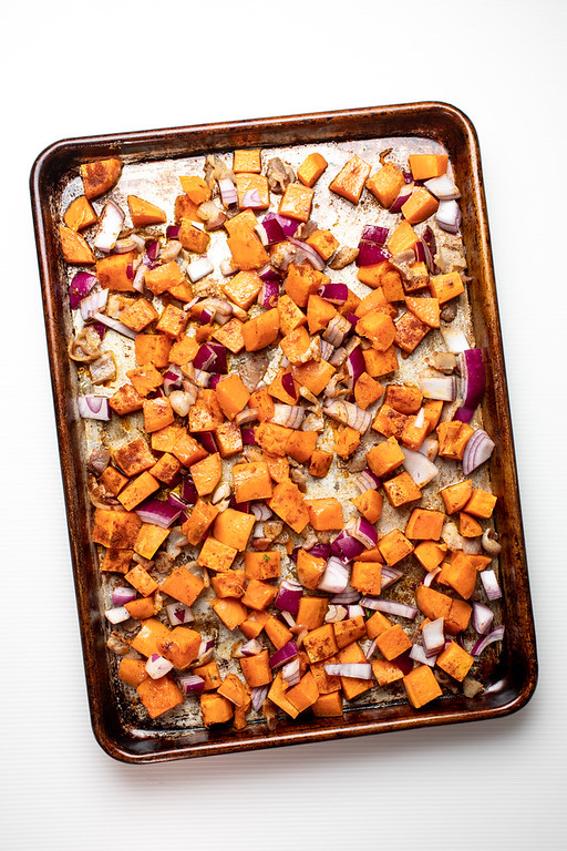 Sheet pan with diced sweet potatoes, onions, and bacon.