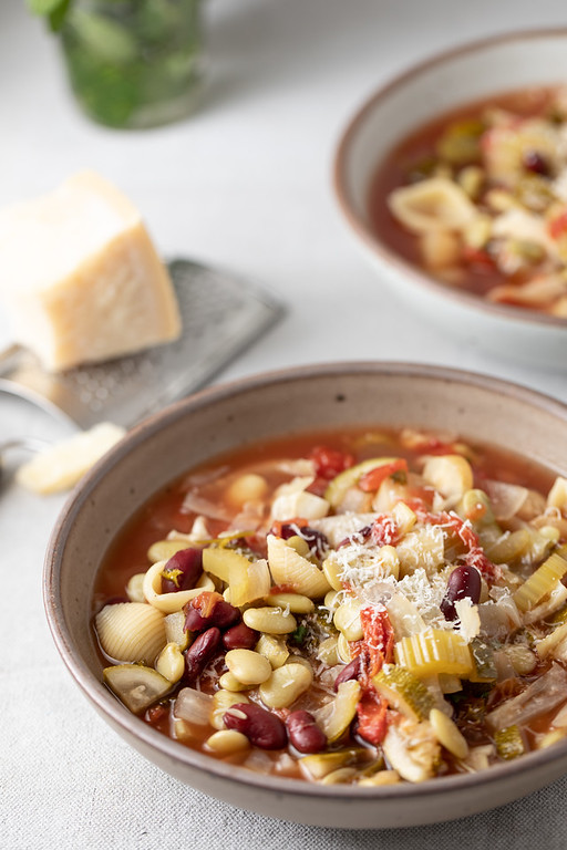 Two bowls of slow cooker minestrone garnished with Parmesan Cheese.