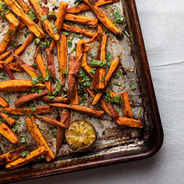 Sweet potato fries on a try with cilantro and lime half.