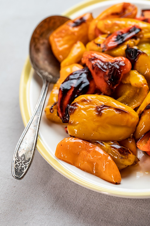 Plate of roasted peppers with a spoon.