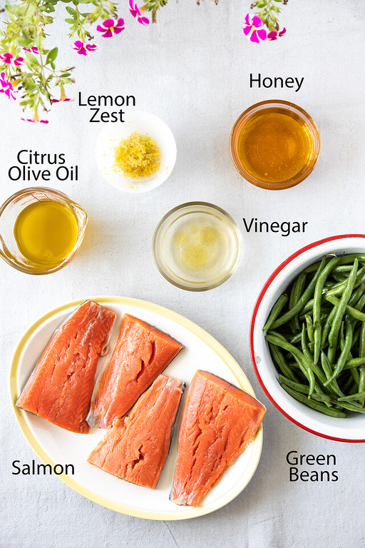 Small bowls of honey, lemon zest, citrus olive oil, vinegar and green beans with a plate of uncooked salmon.