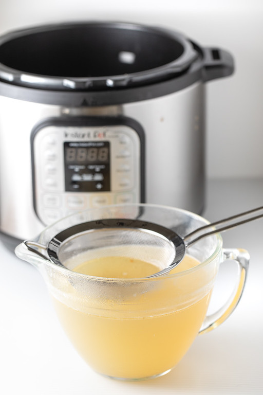 Chicken stock straining into a bowl in front of an Instant Pot.