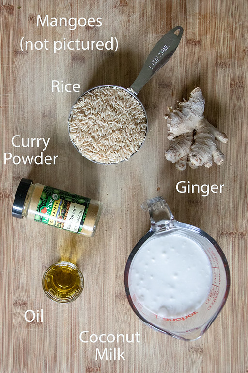 Ingredients needed to make curried mango rice on a wooden cutting board.