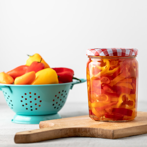 Jar of pickled peppers in front of a bowl of peppers.