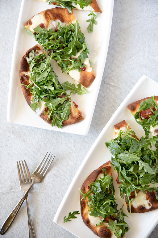 Two plates with prosciutto and arugula naan pizza.