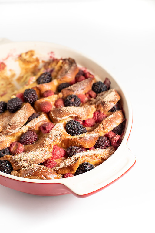 Red casserole filled with baked french toast with blackberries and raspberries.