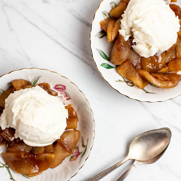 Two bowls of pan fried apples with vanilla ice cream on top.