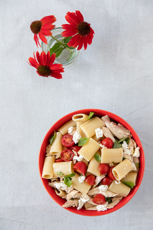 Red bowl filled with pasta, tomatoes, cheese and fresh basil.