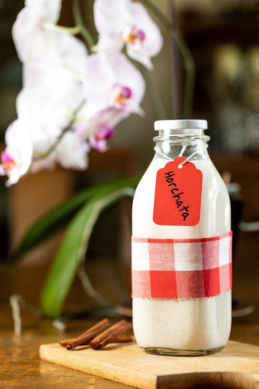 Glass bottle filled with white liquid and tag reading horchata.