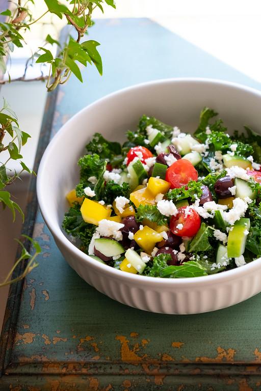 Kale Greek Salad on a blue table.